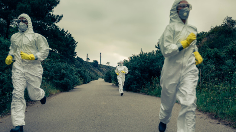 People in biological protection suits running
