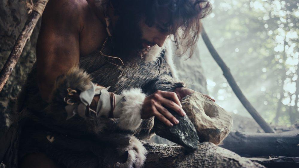 Primeval Caveman Wearing Animal Skin Hits Rock with Sharp Stone