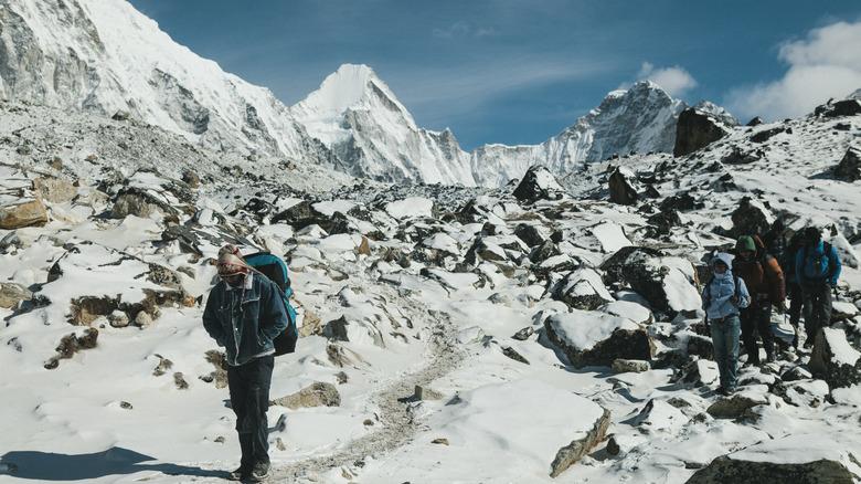 Mount Everest trekkers walking of snow-capped rocks