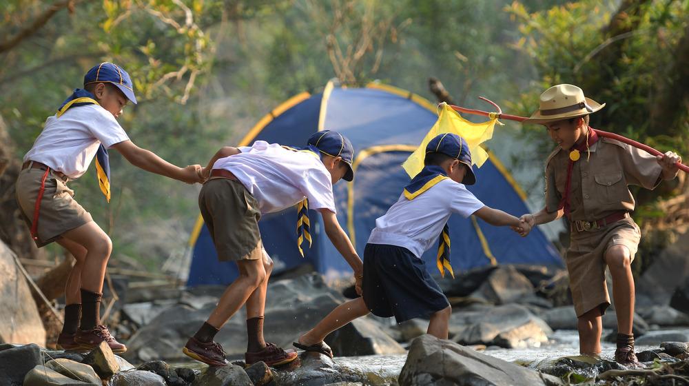 Boy Scout assists Cub Scouts