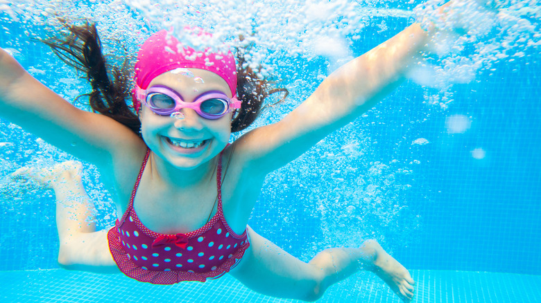 Girl swimming underwater and smiling