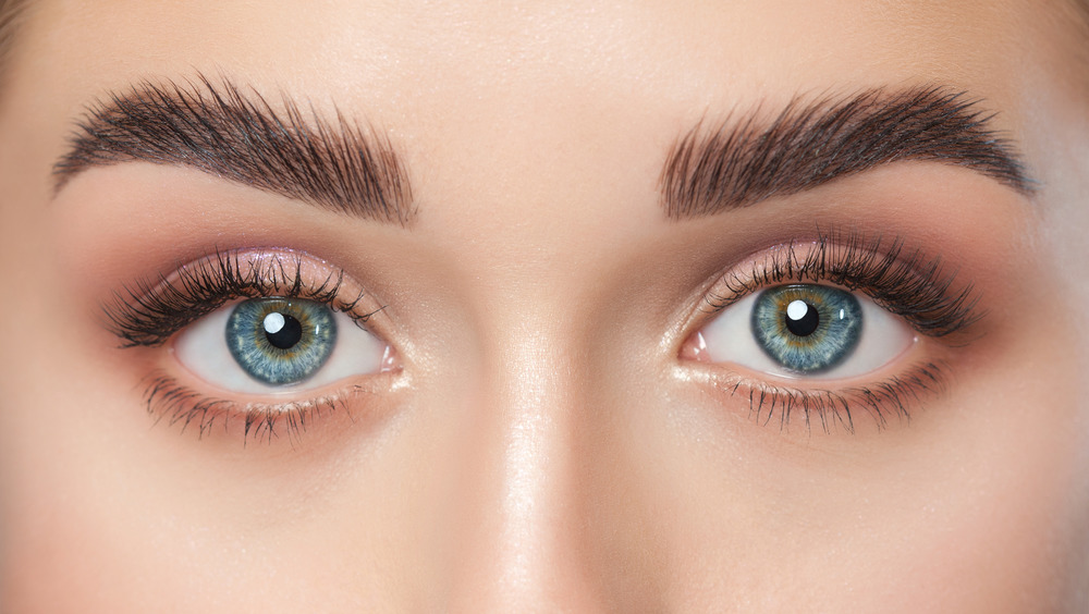 A blue-eyed lady peers out from genetically mutated eyes