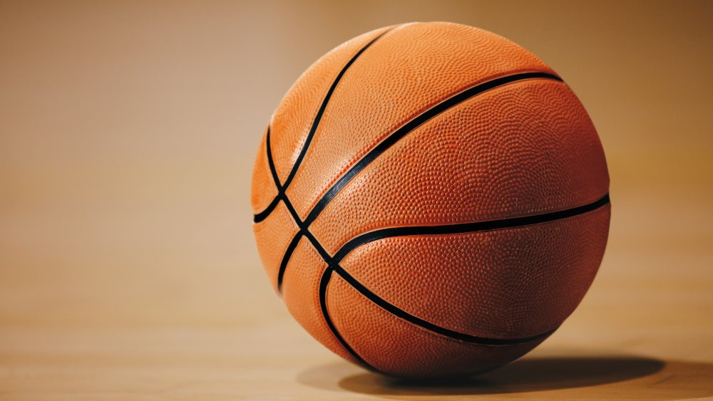 A basketball waits on an empty court