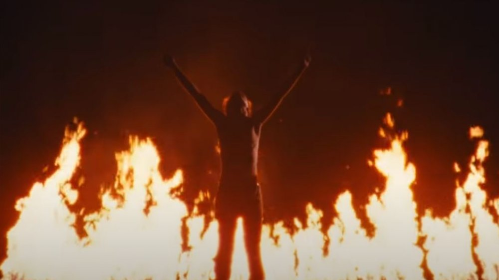 """The young man Jeremy lifts his arms in front of fire in """"Jeremy"""" by Pearl Jam"""