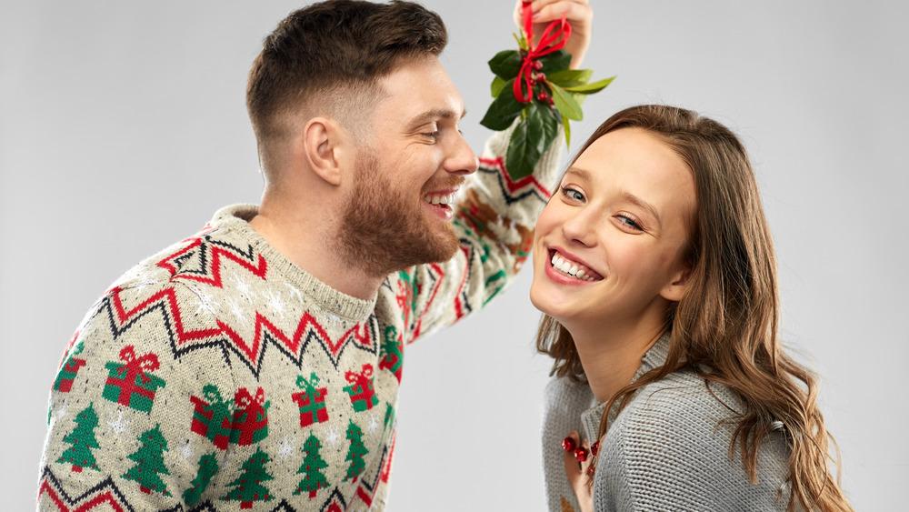 People kissing under mistletoe