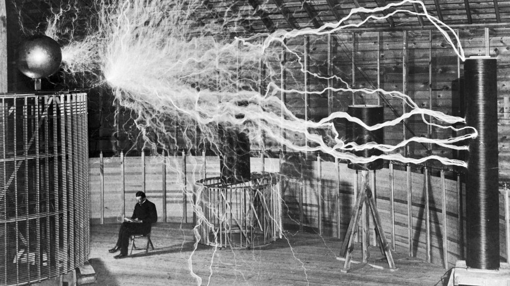 Nikola Tesla with a large electrical device in his laboratory