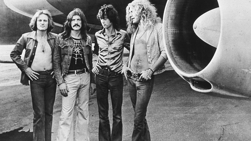 Led Zeppelin posing next to a plane
