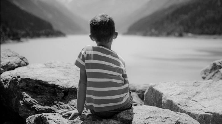 Little boy staring at lake