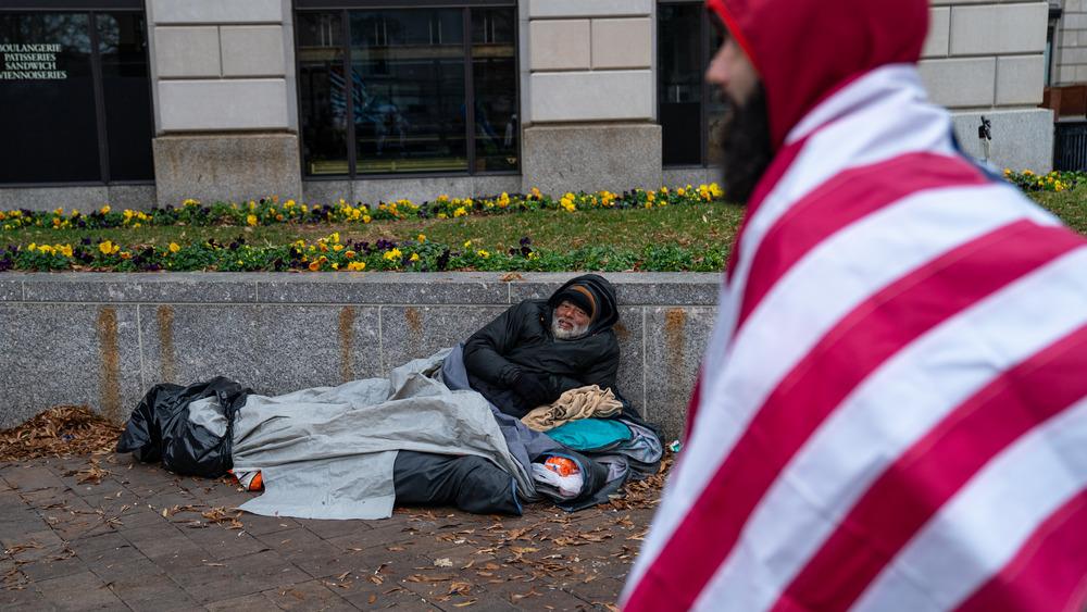 Man wearing US flag walks by homeless man