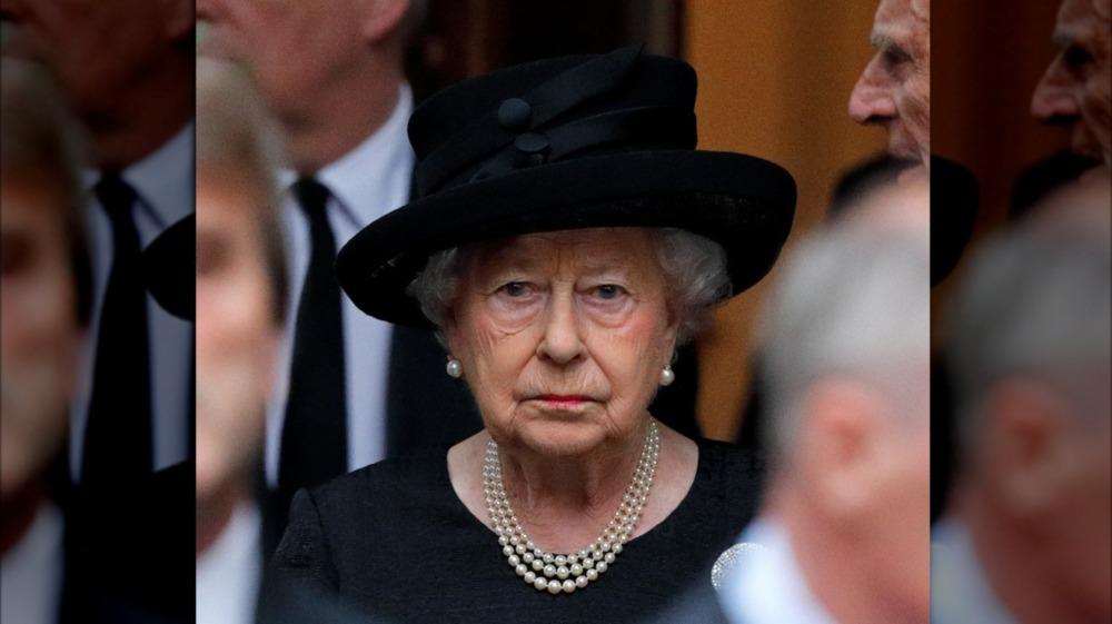 Queen Elizabeth wears a black outfit.