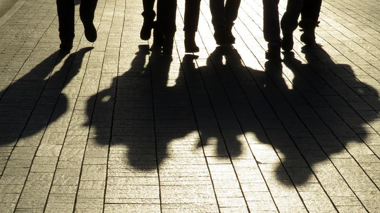 Ominous shadows of people walking