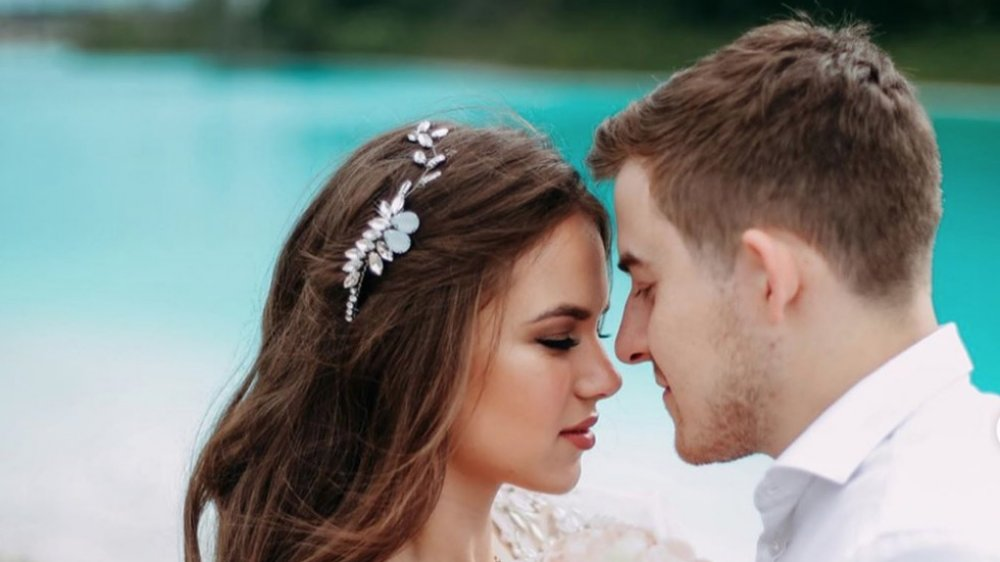 dangerous social media photo, bride and groom posing in front of bright blue lake