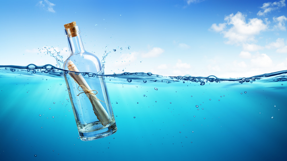 Bottle with message inside floating in water