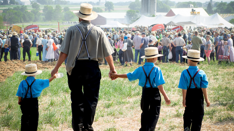 Amish family holding hands