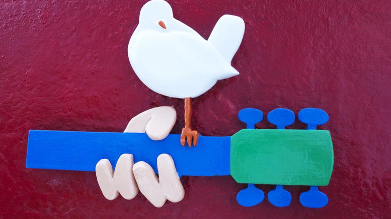 Woodstock dove and guitar symbol