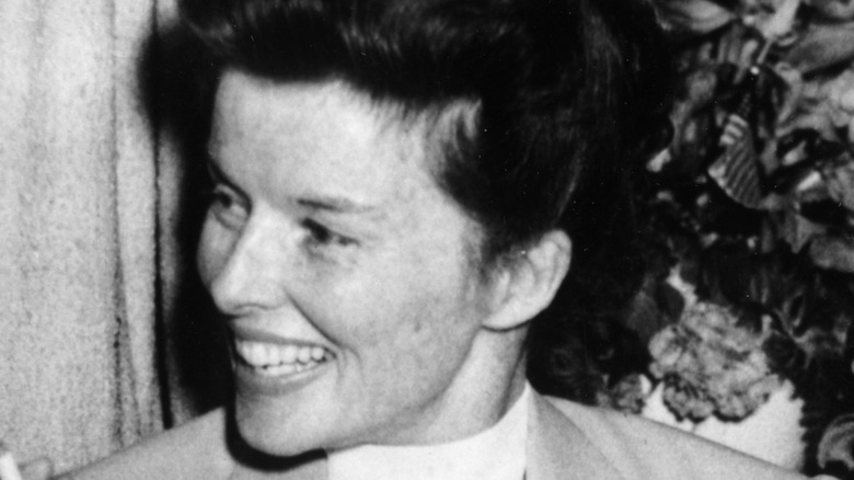 Katharine Hepburn smiling and holding cigarette