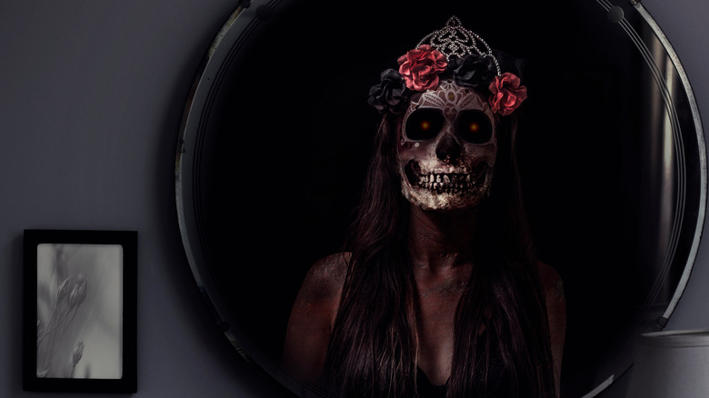 Skeleton with roses on head reflected in mirror