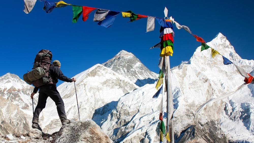 Climber beneath prayer flags on Mt Everest