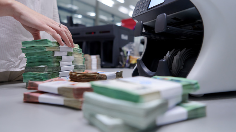 hand of bank teller counting stacks of money