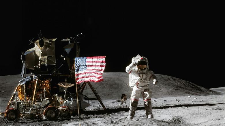 Astronaut saluting next to flag