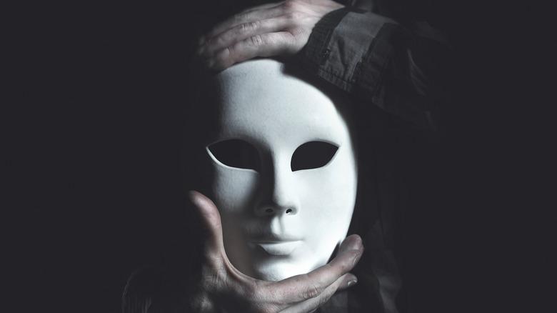 Hands holding white mask