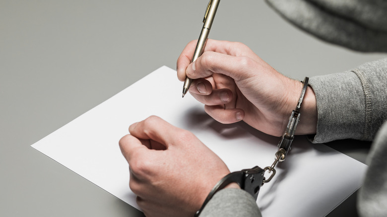 person in handcuffs with pen