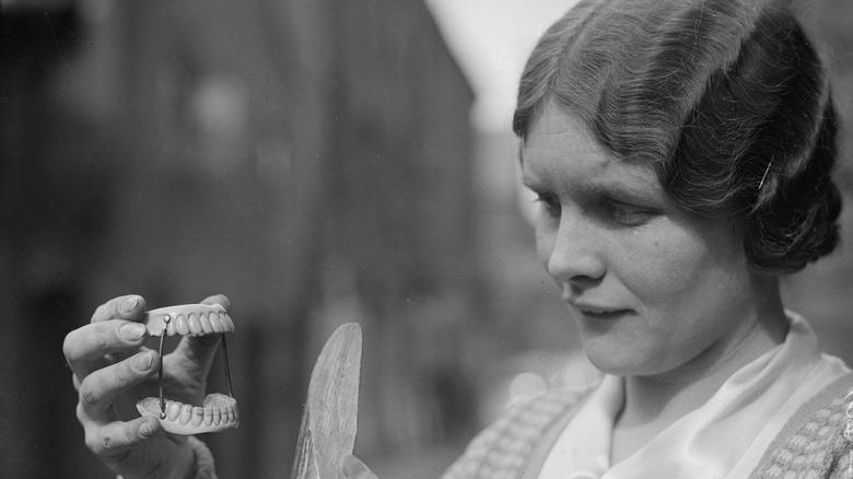 woman looking at false teeth