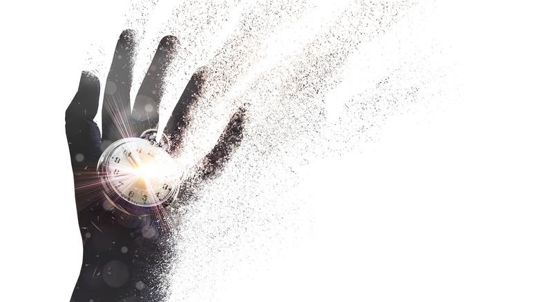 Disintegrating hand holding a timepiece
