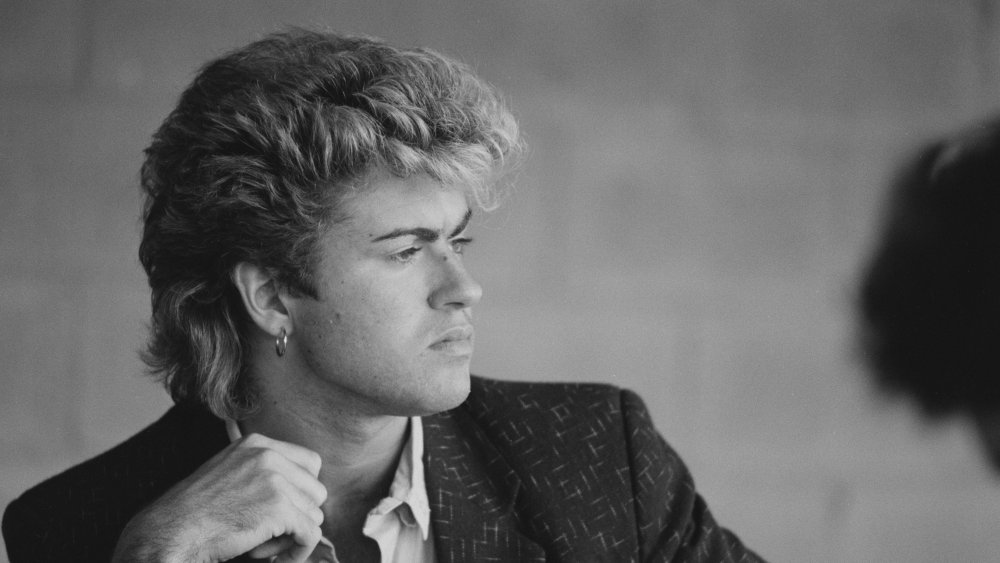 A black-and-white shot of a pensive looking George Michael