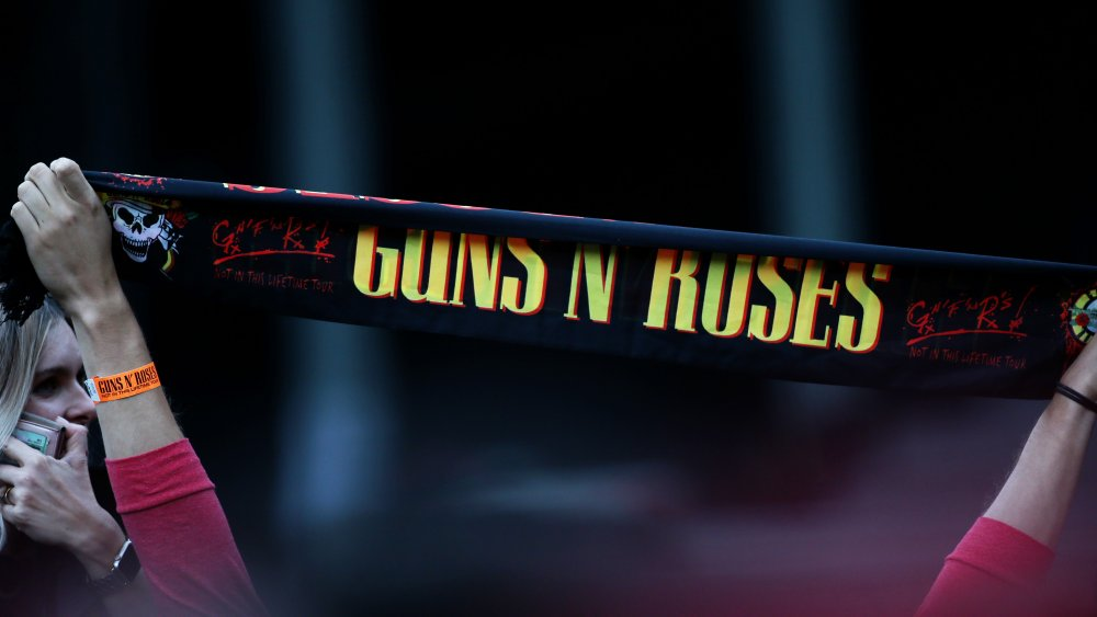 A Guns N' Roses banner held up by a fan at a concert