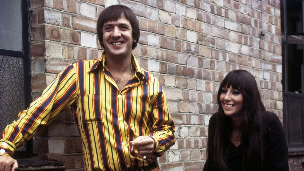 Sonny & Cher pose near a brick wall
