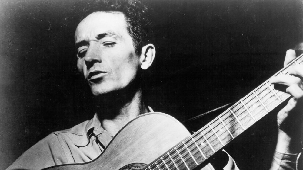 Woody Guthrie holding a guitar
