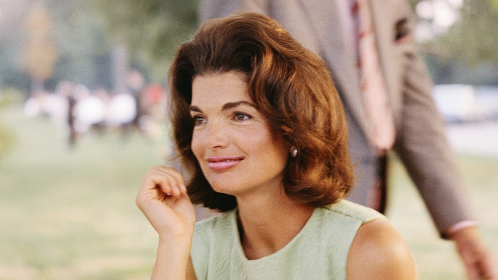 Jacqueline Kennedy Onassis sitting at a picnic table outside in a green dress