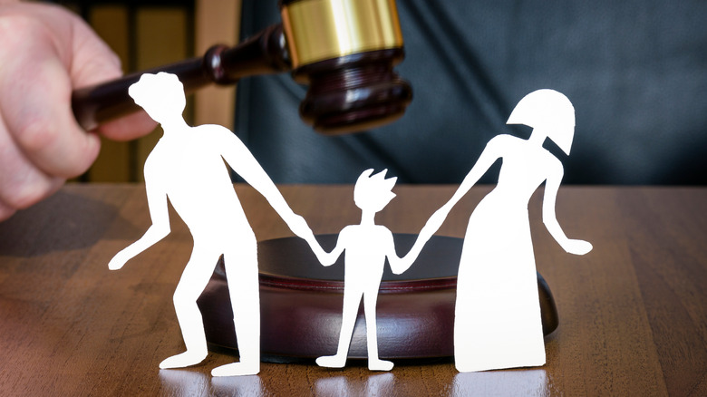 Paper dolls of adults pulling a child with gavel in background