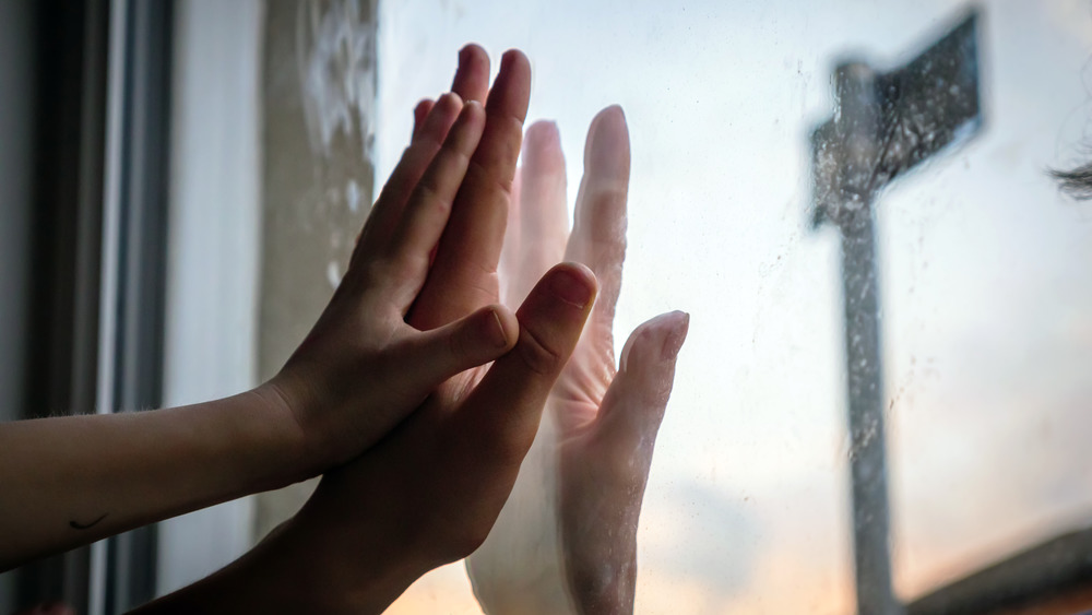 Hands touching on a window