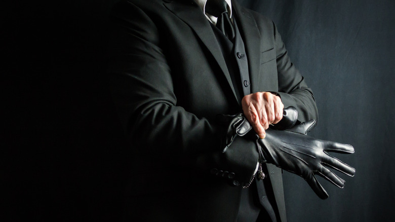 Man in suit pulling on black gloves