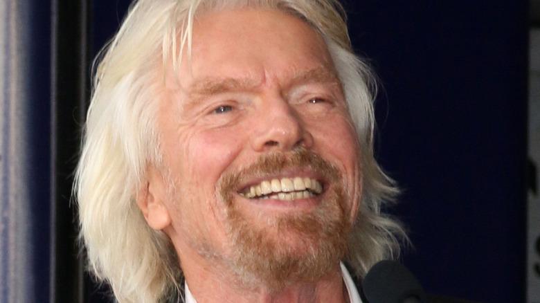 Richard Branson smiles at a podium.