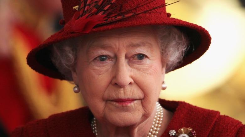 Queen Elizabeth wears red ensemble.