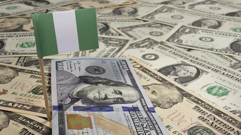 Nigerian flag in pile of dollar bills