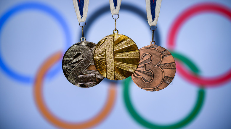 Olympic medals in front of Olympic flag