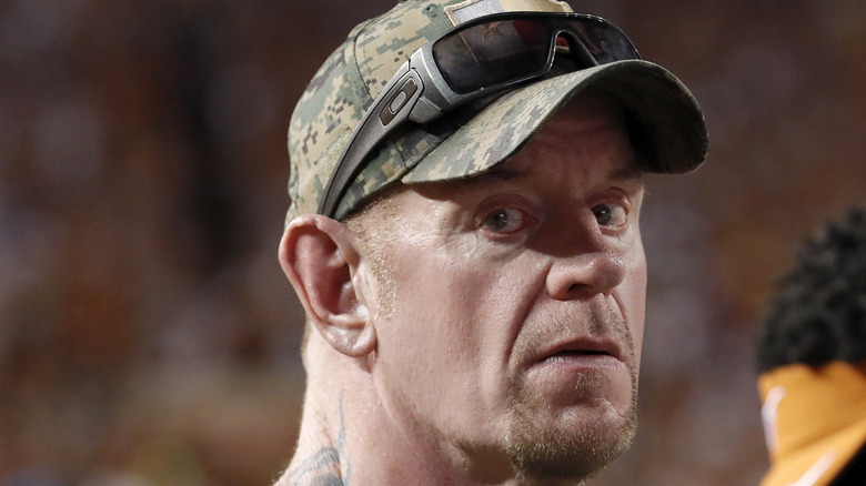 The Undertaker in camo hat looking at camera