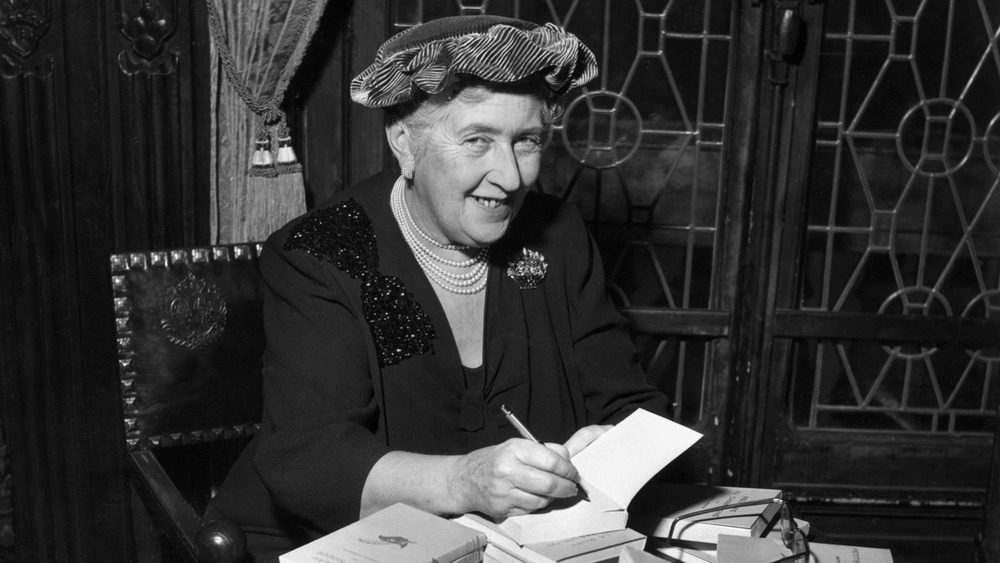 Agatha Christie autographing copies of her book