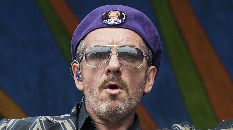 Elvis Costello on stage purple hat