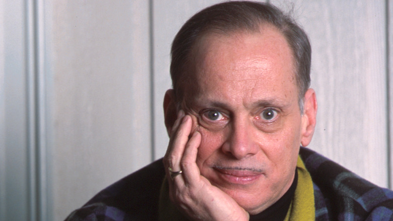 John Waters rests head on hand