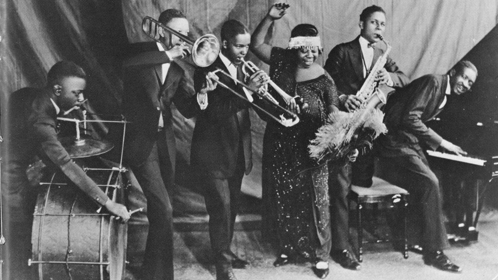 """1924: """"Mother of the Blues"""" Ma Rainey and her band the Rabbit Foot Minstrels with Ed Pollock, Albert Wynn, Thomas A. Dorsey (on piano at right) Ma (Gertrude) Rainey, Dave Nelson and Gabriel Washington pose for a portrait circa 1924 in Chicago, Illinois."""