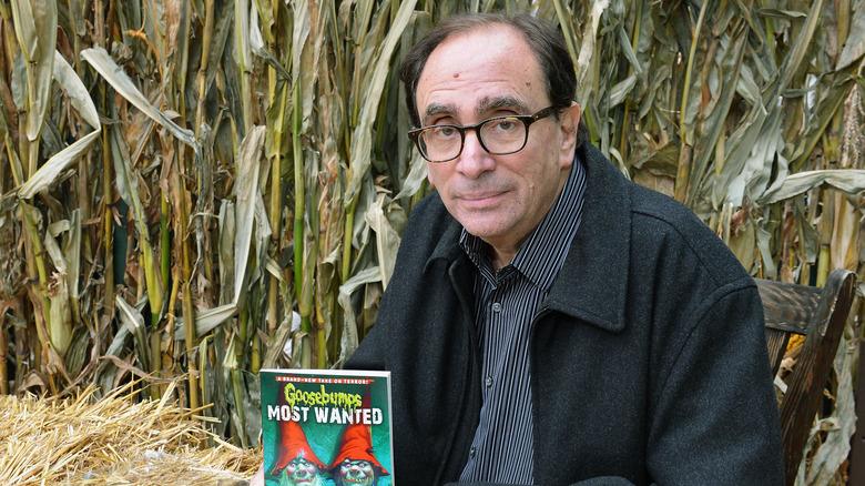 R.L. Stine in field holding Goosebumps