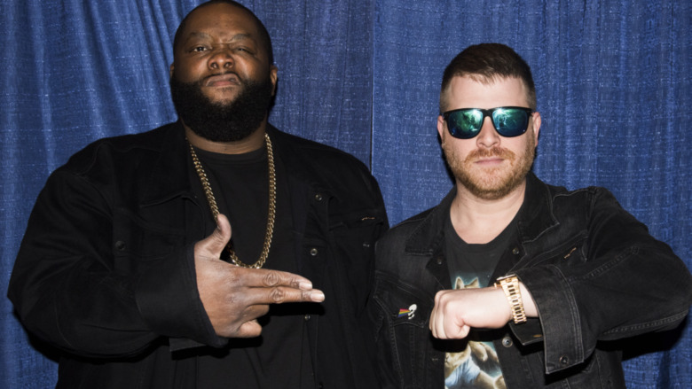 Run the Jewels posing with their hand sign