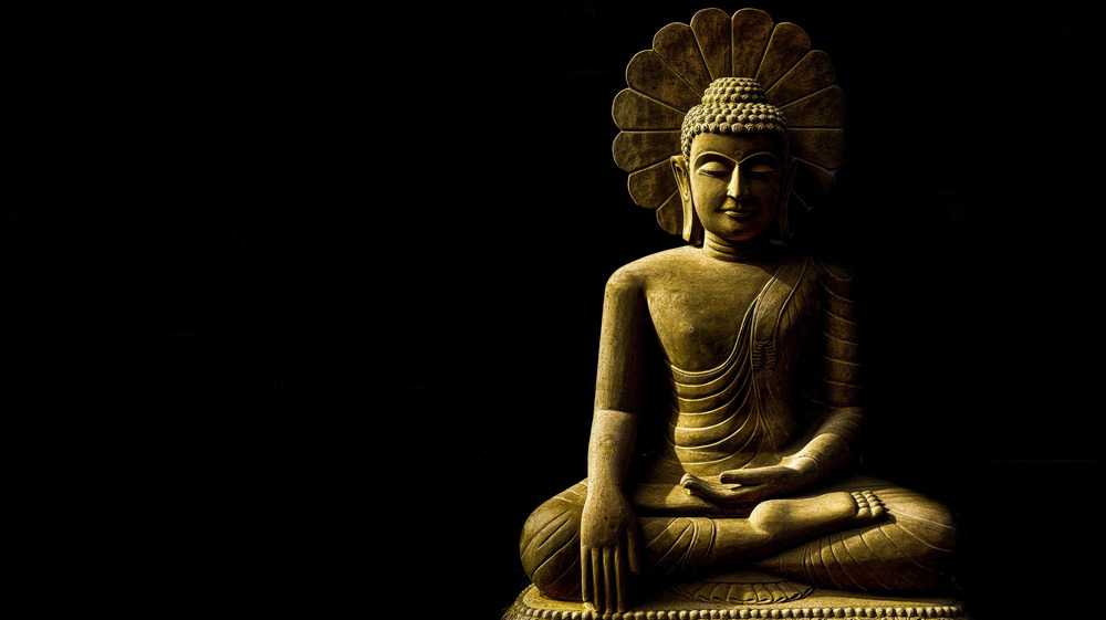 Buddha meditating against dark background