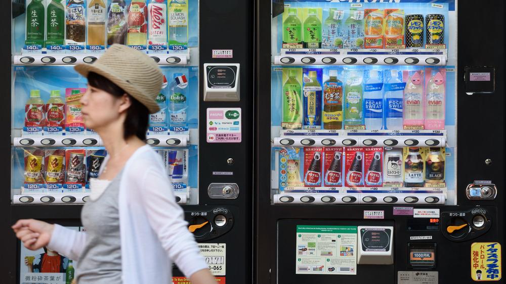Woman strolling past vending machines