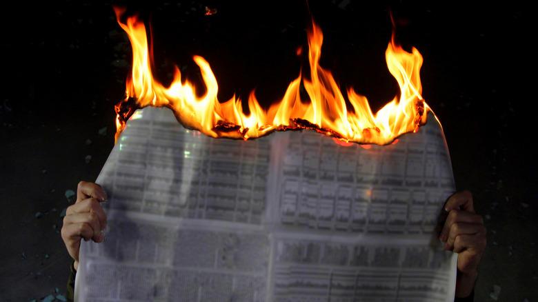hands holding burning newspaper